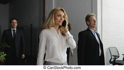 Businesswoman Boss Talking On Phone Call Walking With Her...