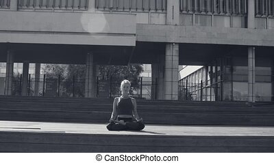 Young woman meditating against modern building - Young woman...