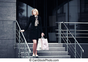 Young fashion woman with shopping bags on the mall steps