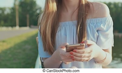 A young girl is typing on the phone and smiling
