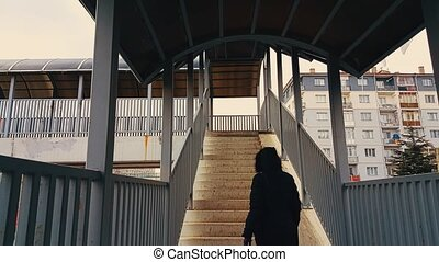 Woman with black coat walking up the stairs of the...