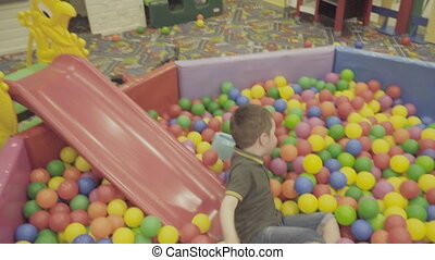 Children play in a big pile of balls - Boy and girl playing...