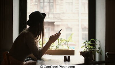 Young stylish woman in hat sitting near the window in cafe...
