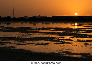 Sunset on the pond of pink flamingos in Chia, Sardinia. -...