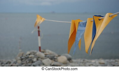 Decorative flags fluttering in the wind on the beach. -...