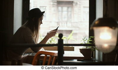 Beautiful young woman sitting at the table near the window and using the smartphone for chatting in social networks.