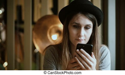 Portrait if beautiful woman sitting in cafe and using the...
