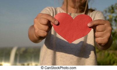Little girl holding a paper heart