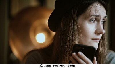 Portrait of attractive young woman holding the smartphone...