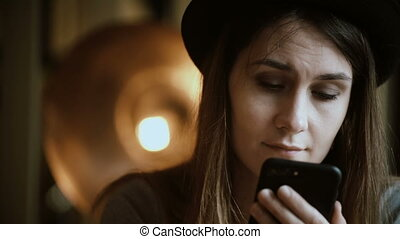 Close-up view of young brunette woman holding the smartphone...