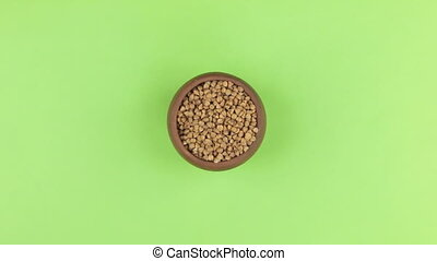 Zoom of a clay pot filled with buckwheat grain. Isolated green screen.