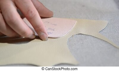 Shoemaker makes pattern on paper and cuts leather -...