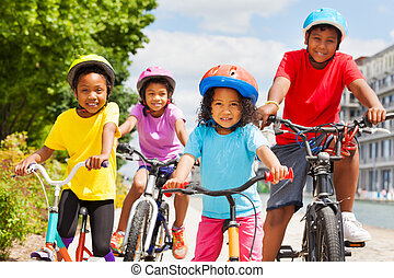 Happy African siblings riding bikes in summer city