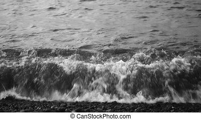 Waves and sea foam - Sea waves crash on the pebbly shore and...