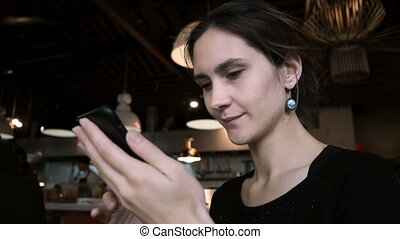 Portrait of young beautiful woman working in cafe. Brunette...