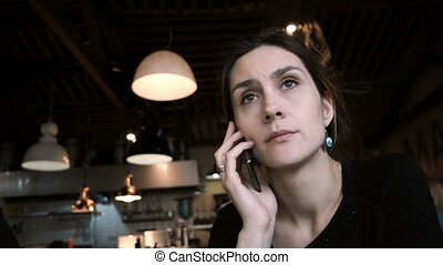 Young beautiful woman sitting in cafe and talking on mobile...