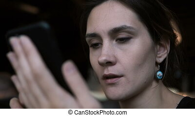 Close-up view of young concentrated woman working on mobile...