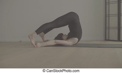 A young woman performing yoga-asanas in the hall. Halassana