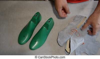 Responsible shoemaker making gray shoes - The responsible...