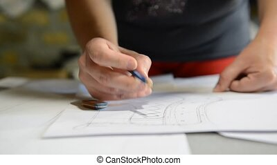 Designer shoes creates a sketch on the paper - Designer is...