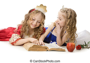 Two beautiful little princesses reading a magic book