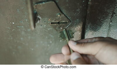 Person key opens the lock on the heavy iron door