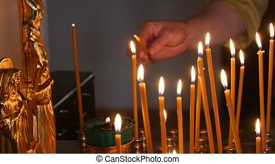 The parishioner put a candle inside an Orthodox church,...