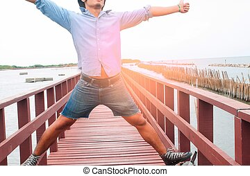 Happy man in casual jeans on wooden bridge, Travel concept
