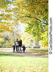 Family with children walking in autumn park