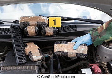 Police officer holding drug package discovered in engine...