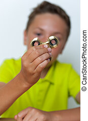 Closeup of 12 years old boy playing fidget spinner - Closeup...