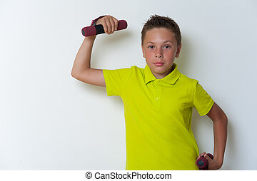 Portrait of 12 years old boy lifting dumbbell, posing on...