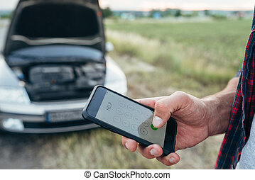 Male person hand with phone, broken car with open hood....
