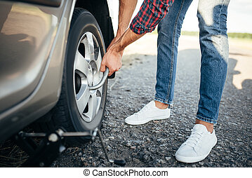 Male person hands with wheel wrench, broken car. Vehicle...