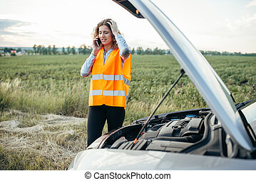 Girl in reflecting vest with phone, broken car - Young girl...