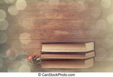 pine branch and books on wooden table.