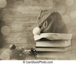 Santas hat and pine brench with books on wooden table.