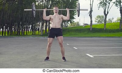 Crossfit. A young man is lifting barbell outdoors