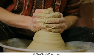 3 shots. Professional male potter working with clay on...