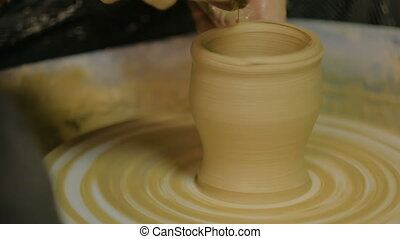 Professional potter shaping mug with special tool in pottery...