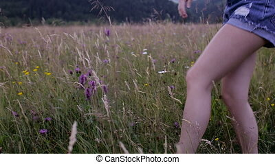 Girl picking a flower on a mountain meadow.