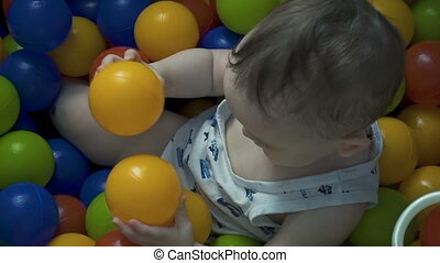 Little boy playing with color balls