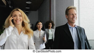 Business Woman Talking On Phone Call Walking With Mix Race Business People Team Through Modern Creative Office Building
