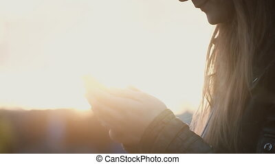 Close-up view of female hands holding the smartphone on the street. Woman using the wireless technology on sunset.