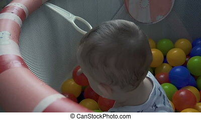 Baby playing with color balls in playpen