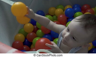 Child playing with color balls in playpen