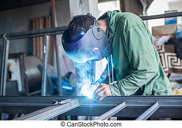 Industrial welder working a welding metal with protective mask