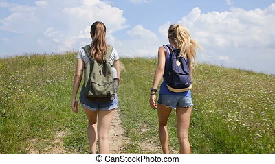 Two young woman walking on mountains