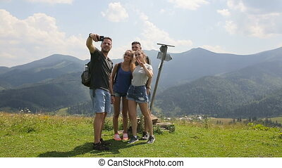 Travelers do selfie in the mountains next to the signpost.