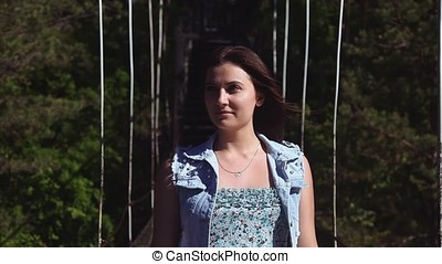 Portrait. The girl is walking along the rope bridge and...
